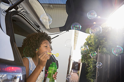 African American girl blowing bubbles in car hatchback in driveway - p1192m1418603 by Hero Images