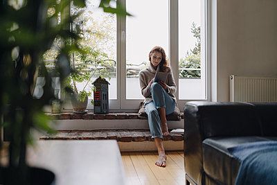 Mature woman sitting on wondow sill, using digital tablet - p300m2155350 by Joseffson
