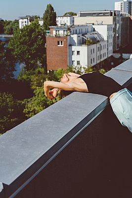 Junge Frau dehnt sich auf Hausdach - p432m2231518 von mia takahara
