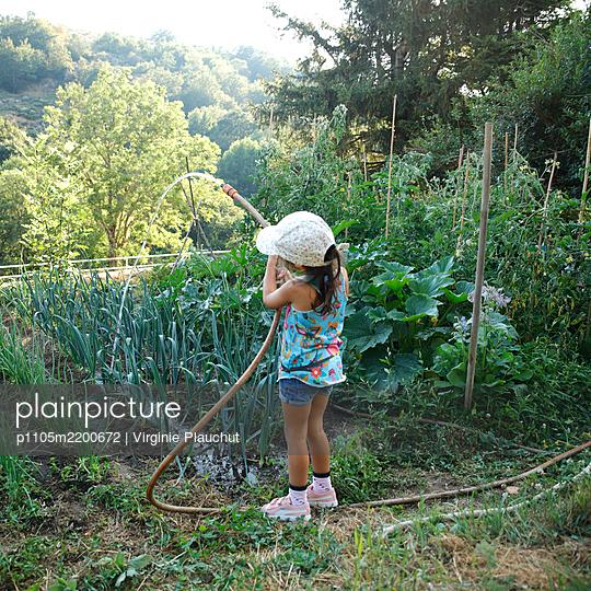 Little girl in the garden - p1105m2200672 by Virginie Plauchut