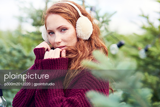 Portrait of redheaded young woman with freckles wearing ear muff and knit pullover - p300m2012220 von gpointstudio