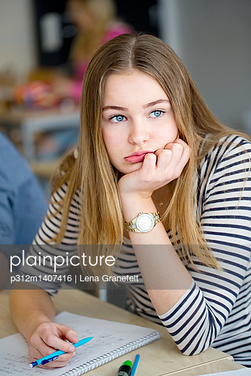 Portrait of bored teenage girl in classroom - p312m1407416 by Lena Granefelt