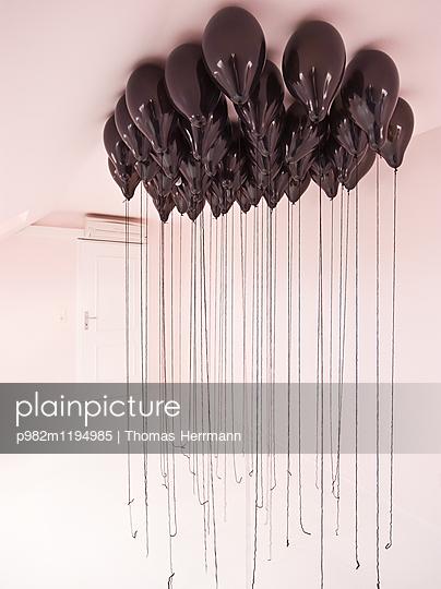 Black balloons at ceiling - p982m1194985 by Thomas Herrmann
