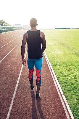 Rear view of sportsman walking on running tracks - p1166m1088138f by John Trice