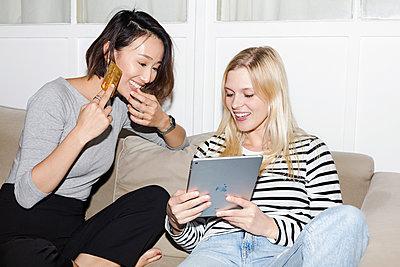 Zwei Freundinnen sitzen auf einem Sofa und betreiben amüsiert Online Shopping - p1301m2020986 von Delia Baum