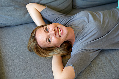 Laughing young woman relaxing on couch - p300m2042894 by Philipp Nemenz