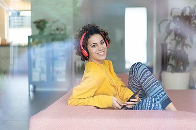 Happy woman listening to music on couch at home - p300m2080326 von Joseffson