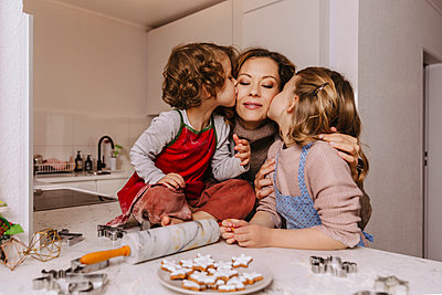 Girls kissing mother in kitchen with Christmas cookies on counter - p300m2155587 by Mareen Fischinger