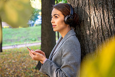 Female entrepreneur contemplating while listening music with smart phone in park during autumn - p300m2241359 by Vasily Pindyurin