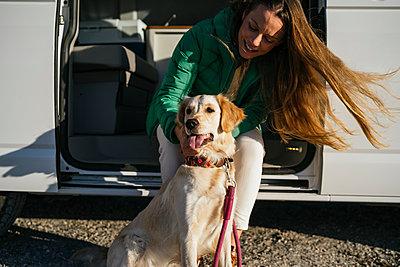 Mid adult woman stroking dog sitting at camper van during sunny day - p300m2266999 by Manu Padilla Photo