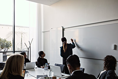 Colleagues looking at businesswoman writing on whiteboard during meeting in board room - p426m2117075 by Maskot