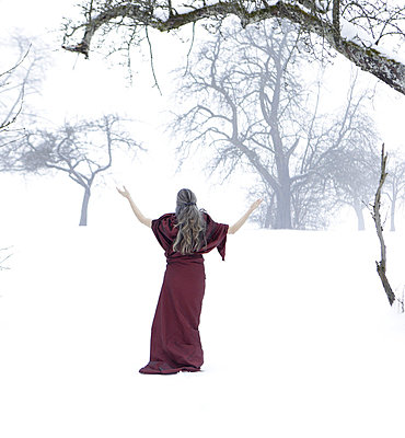 Woman in the snow with a red robe - p5020239 by Tomas Adel