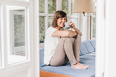 Mature woman having a cup of coffee on sofa - p586m1178527 by Kniel Synnatzschke