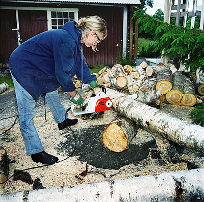 Woman Chopping Wood With Chainsaw  - p847m1529191 by Mikael Andersson