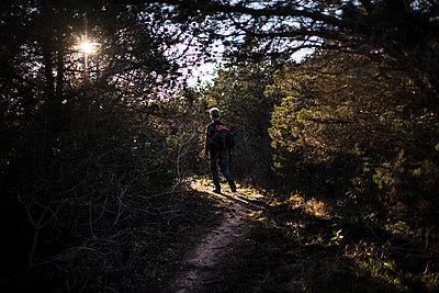 Man walking in nature to the sun - p1007m1540380 by Tilby Vattard