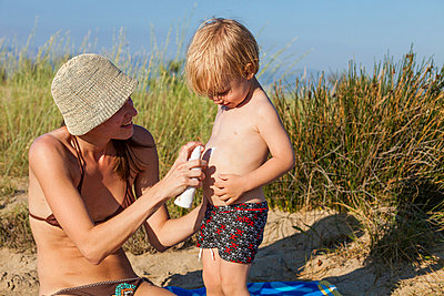 Croatia, Dalmatia, Mother Spraying Sun Block Lotion On Her Sons Belly - p1026m762584f by Dario Secen