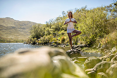 Young woman practising yoga on a riverbank - p1355m1574224 by Tomasrodriguez