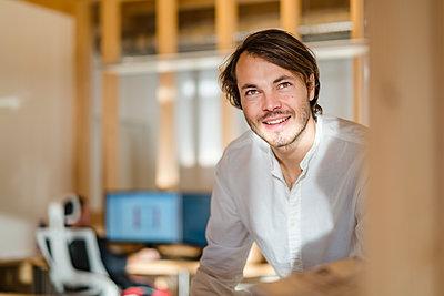 Portrait of smiling businessman in wooden open-plan office - p300m2170060 by Daniel Ingold