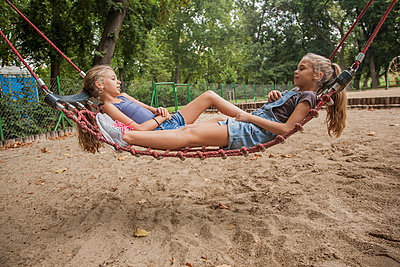 Girls relaxing on rope swing at playground - p300m2239971 by LOUIS CHRISTIAN