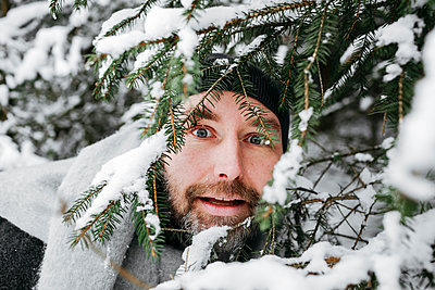 Curious man looking through snow covered pine twigs - p300m2256425 by Katharina Mikhrin