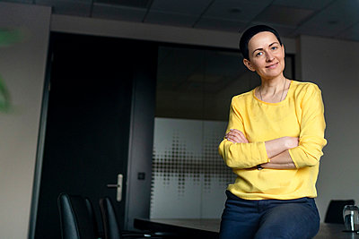 Confident businesswoman with arms crossed at office - p300m2276984 by Oxana Guryanova