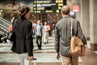 Business people with luggage walking on railway station - p426m844671f by Maskot