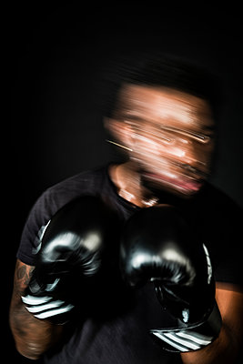 Moving portrait of a boxer fighting on the ring - p590m1516112 by Philippe Dureuil