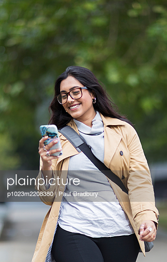 Smiling woman walking with smart phone - p1023m2208380 by Paul Bradbury