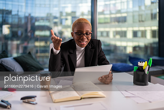 Black businessman discussing work with online colleague - p1166m2279416 by Cavan Images
