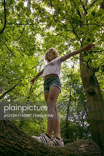 Mädchen balaciert auf einem Baumstamm - p1212m1152987 von harry + lidy