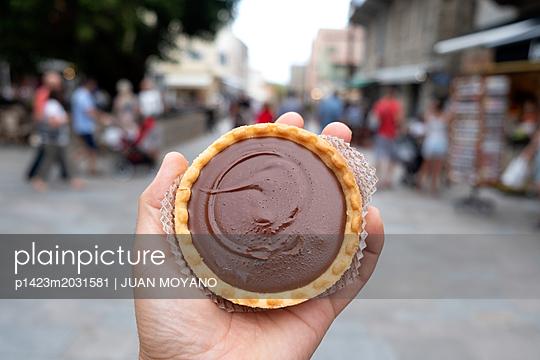 Mann mit Schokoladengebäck auf der Straße - p1423m2031581 von JUAN MOYANO