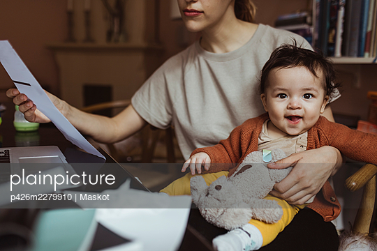 Portrait of smiling baby boy with businesswoman at home office - p426m2279910 by Maskot