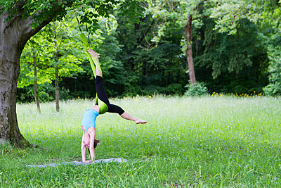 Young woman does stretching exercises with rubber band, Munich, Bavaria, Germany - p1026m996447f by Patrick Frost