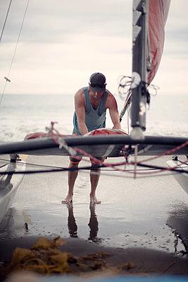 Man standing on beach next to catamaran - p1166m1080298f by Jessica Weber