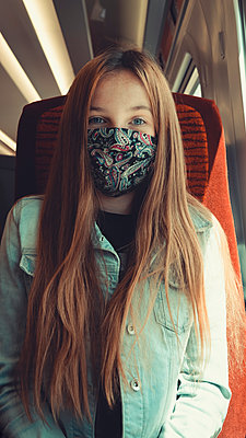 happy girl on transport wearing a mask looking into camera - p1166m2247966 by Cavan Images