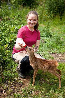Junge Frau füttert Rehkitz - p1195m1071087 von Kathrin Brunnhofer