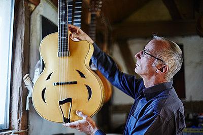 Gitarrenbauer untersucht eine E-Gitarre in seiner Werkstatt - p1359m1221830 von Great Images
