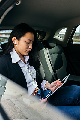 Young businesswoman sitting in car using earpods and digital tablet - p300m2189294 by Xavier Lorenzo