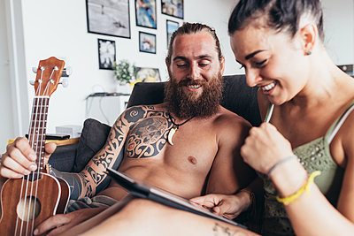 Bearded tattooed man with long brunette hair and woman with long brown hair sitting on a sofa, looking at digital tablet. - p429m2201555 by Eugenio Marongiu