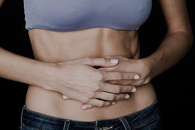 Woman clutching bare stomach with hands - p623m1506979 by Frederic Cirou