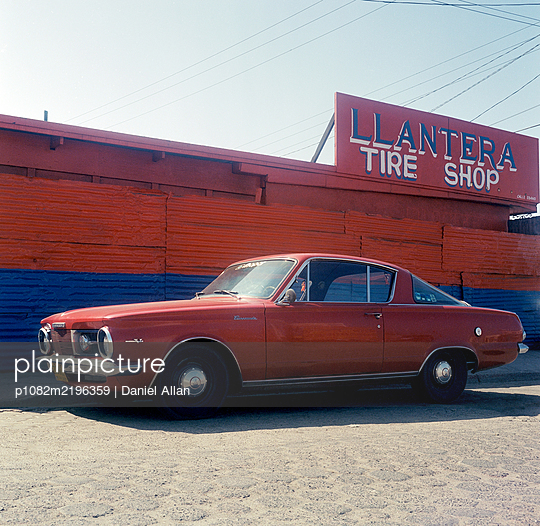 Red oldtimer in front of tyre service - p1082m2196359 by Daniel Allan