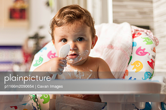 baby stained with yogurt while eating yogurt in his high chair to eat - p1166m2090654 by Cavan Images
