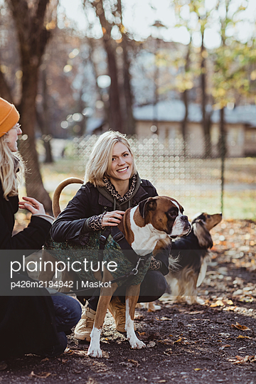 Portrait of smiling blond woman crouching by friend with dogs at park - p426m2194942 by Maskot