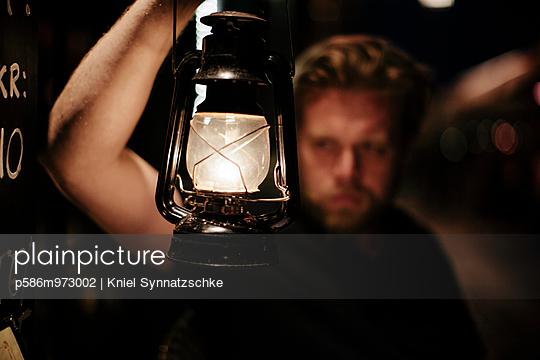 Mann hält eine Öllampe in der Hand - p586m973002 von Kniel Synnatzschke