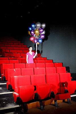 Woman with colourful balloons in vintage cinema hall - p1105m2254512 by Virginie Plauchut