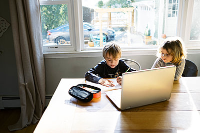 kids in morning light sitting at table doing remote school - p1166m2232721 by Cavan Images