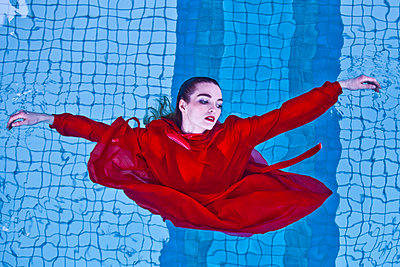 Woman in red dress in swimming pool - p1413m2150608 by Pupa Neumann