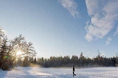 Mature woman walking through the snow in Ostergotland, Sweden - p352m2120028 by Åke Nyqvist