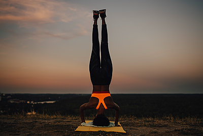 Sportswoman practicing yoga during sunset - p426m2270805 by Maskot