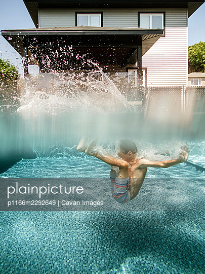 Split view of a 7 years old boy jumping in a pool at home - p1166m2292649 by Cavan Images